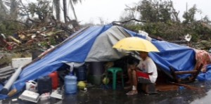 A typhoon victim sits under an umbrella outside a makeshift tent after Super Typhoon Haiyan battered Tacloban city in central Philippines