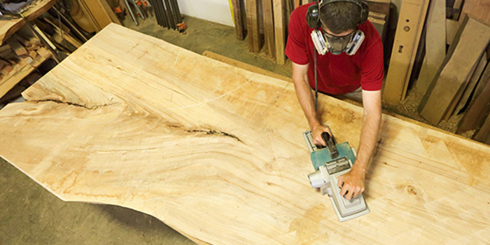 Urban Hardwoods craftsman sanding and prepping a section of trunk.