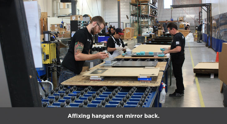 Affixing hangers on mirror back, and packaging